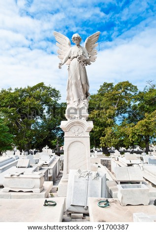 Statue of a beautiful angel on a bright day with a cemetery background