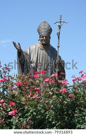 Statue of Pope John Paul II in rose garden - stock photo