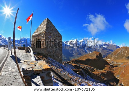 Steep turns are marked with red flags. Picturesque alpine road Grossglocknershtrasse. Bright sunny day. Photo taken by lens Fisheye - stock photo