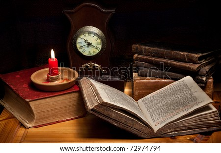 Still life with old books,Greek Gospel, clocks, candle and pipe - stock photo