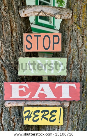 """Stop and eat here"" sign on tree trunk - stock photo"