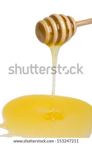 stream of honey on the wooden honey dipper - stock photo