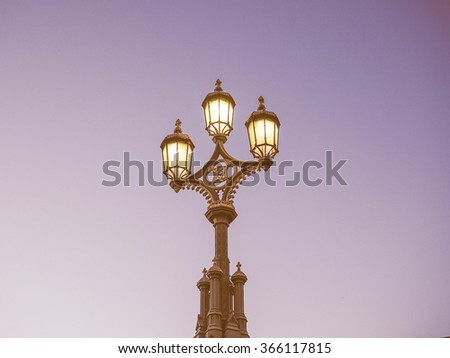 Street light lit lamppost at night over blue sky with copy space vintage