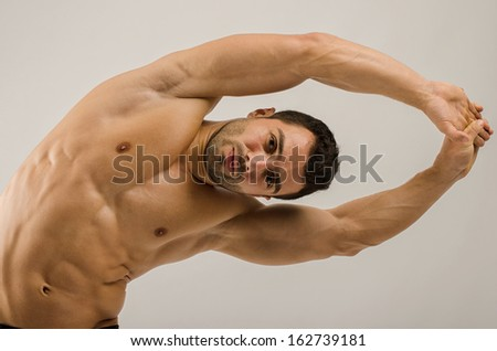 Strong bodybuilder training his six pack. Man doing abs exercise - stock photo