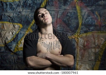 Strong fit male with arms crossed posing over graffiti wall  - stock photo