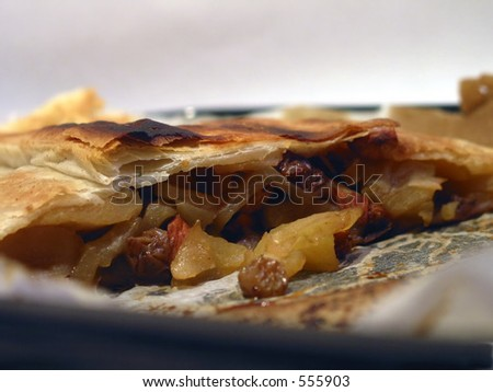 Strudel or hot apple cake made of apples, raisins and honey, traditional jewish food for Rosh Hashana, the new years day. - stock photo