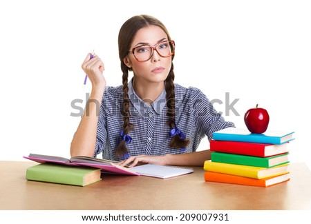 student  girl sit from the table, holding pen and look at camera, near lie big red apple and pile of books, white background - stock photo