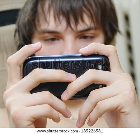 student sending text message using mobile smart phone - stock photo