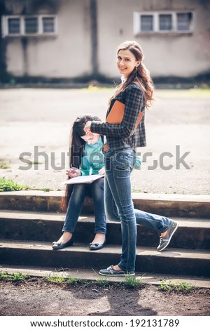 students sitting with a book on street - stock photo