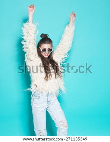studio portrait of cheerful hipster girl in sunglasses going crazy making funny face and dancing. Blue wall background. - stock photo