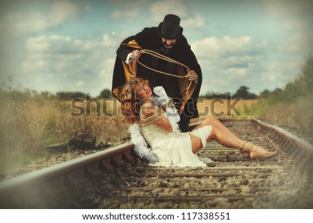 1920 style image of damsel in distress tied up by villain - stock photo