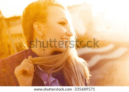 Stylish young beautiful blonde girl on a sunny day in an elegant   with full red lips smiling posing at sunset close-up on a city street Happy Life Style autumn