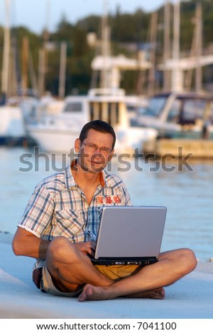 Successful young man with laptop at the port - stock photo
