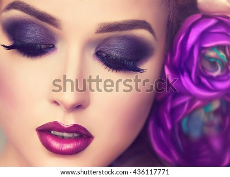Summer  girl. Beautiful model with flower wreath on her head . Purple Makeup smoky eyes . Spring  girl with trendy make up . Hairstyle curly ponytail with violet   artificial rose flowers in  hair . - stock photo