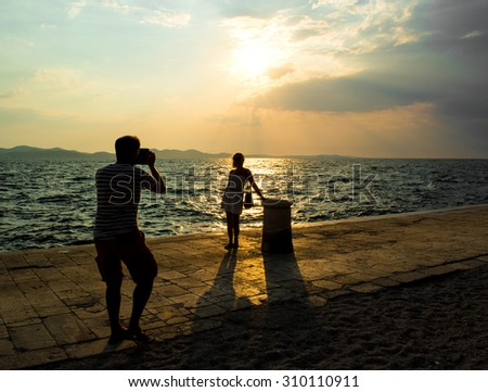 Summer time. Silhouette of man photographing woman outdoor