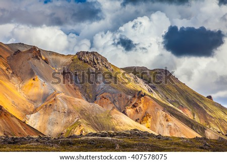 Summer volcanic tundra.  Bright and multi-colored rhyolite mountains - yellow, orange, green and blue. Travel to Iceland in July - stock photo