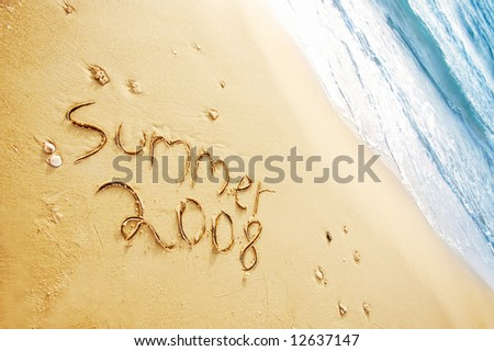 """summer 2008"" written in the sand on the beach blue waves in the background"