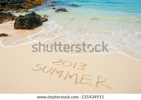 """Summer 2013"" written on sandy beach - stock photo"