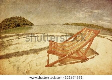 sun beach chair on shore near sea in grunge and retro style - stock photo