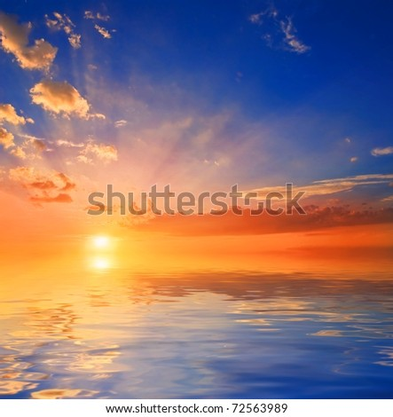 sun going down to a sea - stock photo
