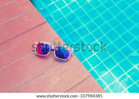 Sunglasses laying beside swimming pool. - stock photo