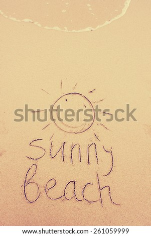 """Sunny Beach"" written on the sand / Summer holidays background - stock photo"