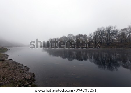 sunrise on the river during the late autumn, mist, cloudy, defocused - stock photo