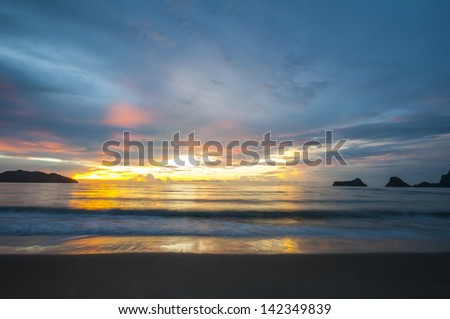 Sunrise over waves and sea with beautiful reflections - taken in Prajoub bay-Thailand. - stock photo