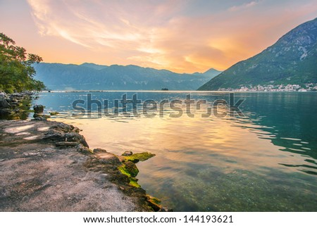 Sunset on the sea with the ���° foggy mountains. Montenegro