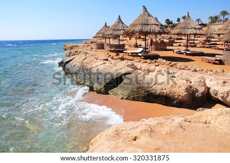 Sunshade umbrellas on the beach with parasols straw sunshades and wooden sunbeds in front of a turquoise on the beach of Red Sea with a waves and blue sky. - stock photo