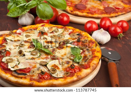 Super healthy vegetables and mushrooms pizza and salami pizza at the back - stock photo