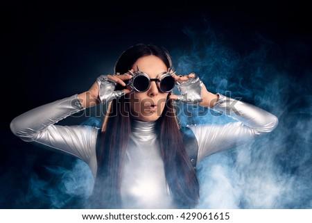 Surprised Woman in Silver Costume and Steampunk Glasses - Portrait of a sci-fi retro futuristic robotic girl   - stock photo