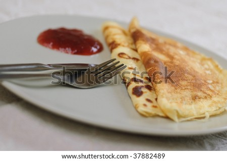 2 swedish pancakes with some jar on the side - stock photo