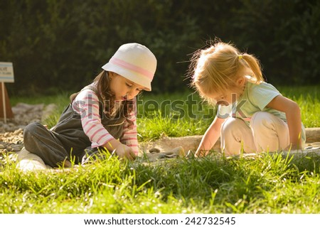 Sweet little girls playing in sand on a sensory garden. Little girls enjoying nature. Outdoors activity. - stock photo