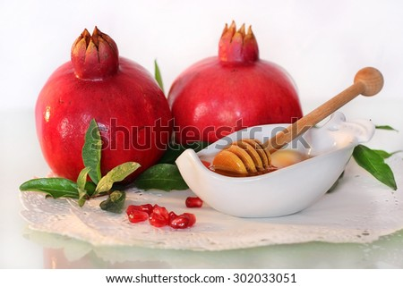 symbols of holiday of Rosh Hashanah, traditional jewish food, honey and pomegranate - stock photo