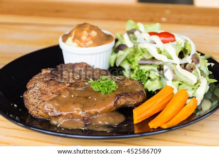 t-bone steak served with mash potato  and fresh green herb salad accompanied by a BBQ sauce.
