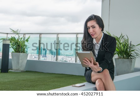 Tablet computer. Woman using digital tablet computer PC happy isolated on white background. Focus on both tablet and face. Beautiful mixed race Asian / Caucasian woman in business shirt. - stock photo