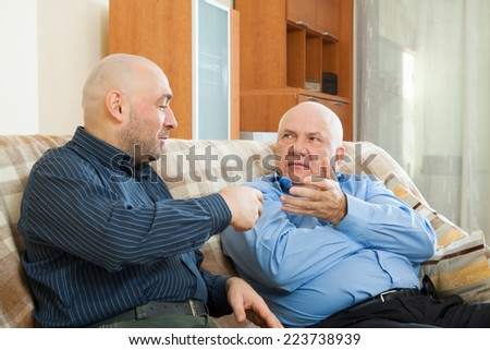 talking men siting on couch at home - stock photo