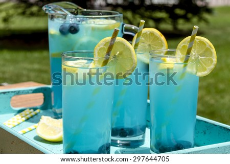 3 tall glasses and pitcher filled with blueberry lemonade with fresh lemons and blueberries and yellow swirled straws sitting in blue drink tray - stock photo