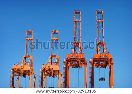 tall orange industrial cranes rising into sky - stock photo
