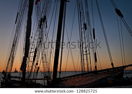 """""""Tall Ship Dawn""""  Sunrise over Lake Michigan viewed through the riggings of the tall ship Roseway moored at Navy Pier. - stock photo"""