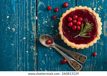 tart with berries jam decorated with cranberry and rosemary, top view - stock photo