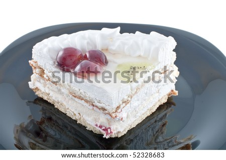 Tasty cake with fruit on black plate