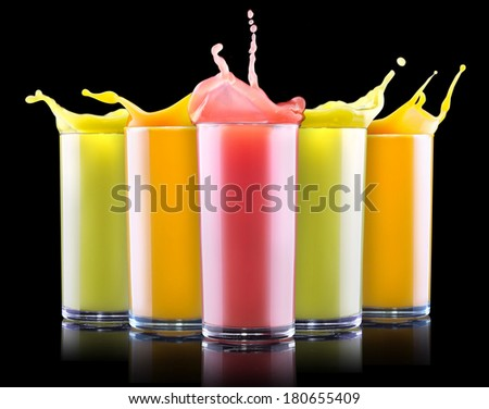 tasty summer fruit drinks in glass with splash isolated on a black background