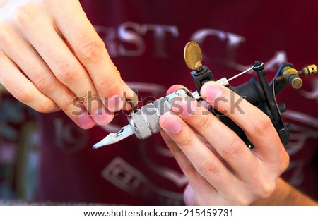 tattooer showing process of making a tattoo, hands holding a tatoo machine - stock photo