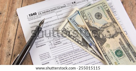 1040 tax form with calculator and dollar bills - stock photo