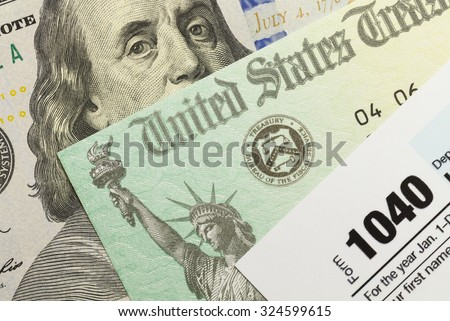 1040 Tax Form with Refund Check and Cash. - stock photo