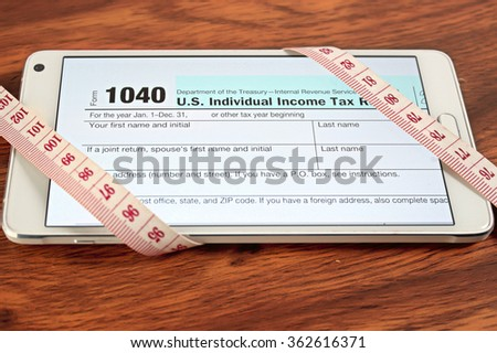 1040 tax forms, look in the phone with a tape measure on wood table / concept of paying taxes online and save.selective focus on 1040 - stock photo