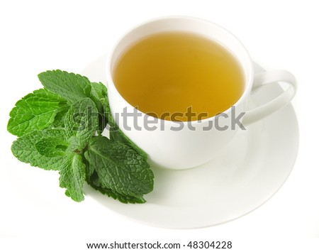 Tea cup with green fresh mint leaves isolated on white background