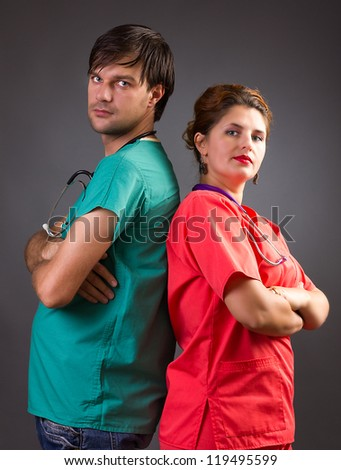 Team of two serious doctors standing back to back with arms folded isolated on grey background - stock photo